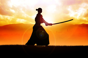 Silhouette of a samurai posing during sunset