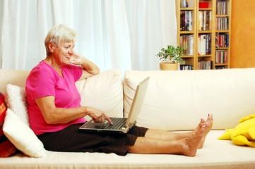 Friendly elderly lady sitting on sofa with laptop