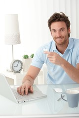 Smiling office worker at desk with phone handheld