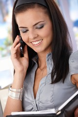Attractive secretary on mobile smiling