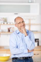 lächelnder mann überlegt etwas in der küche