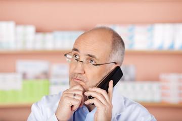 apotheker am telefon blickt ernst
