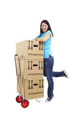 Frau mit Umzugskarton, Karre, auf Fußspitzen stehen