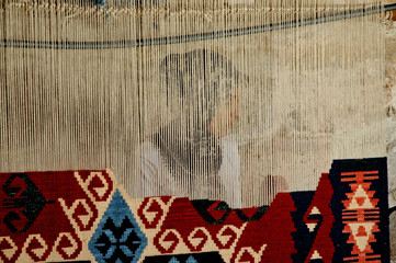 Woman weaves a traditional Turkish carpet