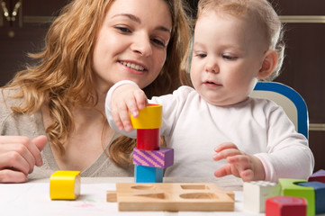 Mother and baby daughter building tower
