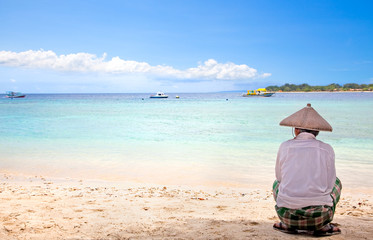 Indonesian man with straw hat sitting on the beach