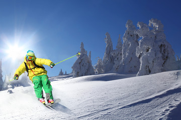Cool skier in high mountains against sunset