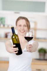 junge frau zeigt rotwein in der küche