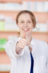 lächelnde apothekerin zeigt daumen hoch
