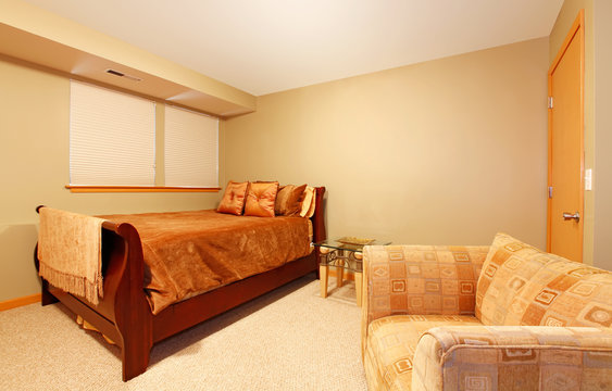 Simple basement level guest bedroom with bed and chair.