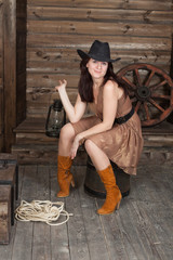 brunette CowGirl with sitting in a old depot