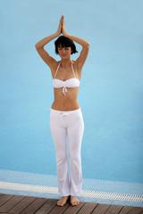 Brunette doing yoga by swimming pool