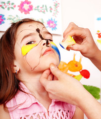 Child with face painting.
