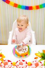 Happy eat smeared baby eating first birthday cake