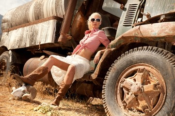 Attractive blond woman near an old truck.