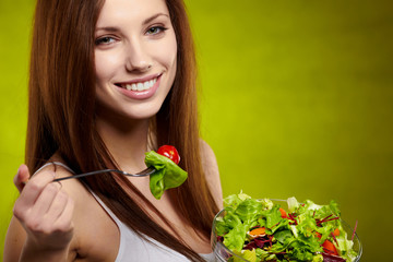 Healthy lifestyle - woman holding vegetable salad on green backg