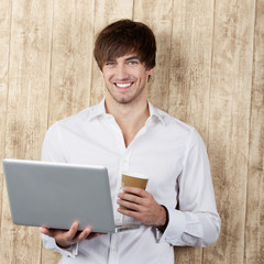 lachender junger mann mit laptop und kaffee