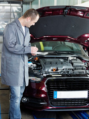 Master mechanic in garage checking engine bay for an offer