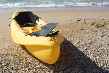 Yellow boat at the beach near the sea water