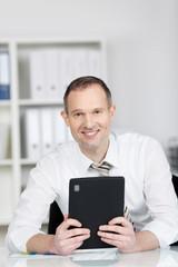 freundlicher geschäftsmann arbeitet mit seinem tablet-pc im büro