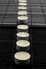 Candles in a row on mat