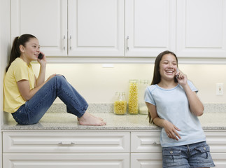 Two teenage girls talking on cell phones
