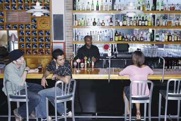 Two young men sitting in a bar looking at a young woman