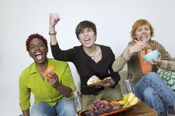 Three women cheering and eating