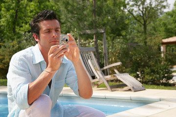Man taking picture near a swimming-pool
