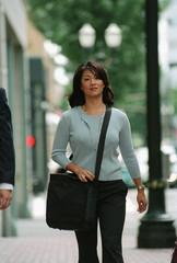 Businesswoman walking down urban street