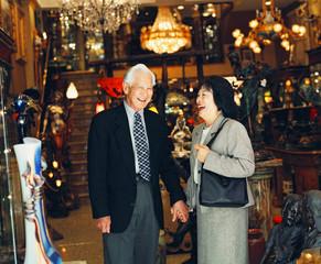 Senior couple holding hands in lighting store