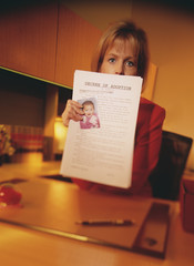 Young woman holding adoption papers