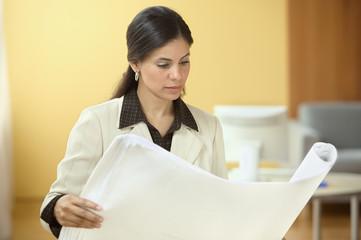 Businesswoman reading blue prints