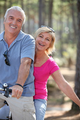 man and woman riding a bike in the forest