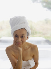 Portrait of senior woman wrapped in towel with towel on head