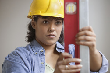 Woman construction worker in hard hat reading level measurements