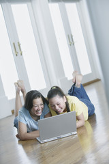 Two teenage girls lying on the floor working on a laptop