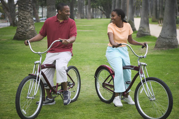 Couple riding bikes in park