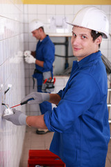 Young electricians wiring wall sockets
