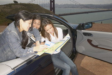 Friends in convertible looking at map