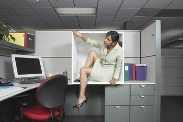 Businesswoman exiting office cubicle