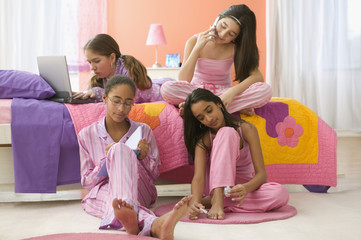 """""""Four girls sitting in bedroom with computer, journal, cell phone and fingernail polish """""""