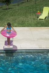 High angle view of girl standing on diving board with innertube