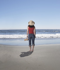 Rear view of woman standing on beach looking at ocean