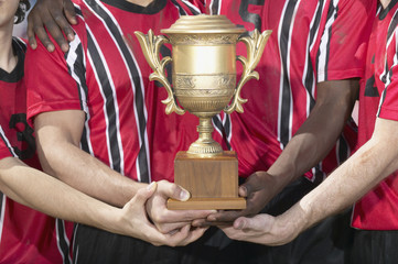 Soccer players holding trophy