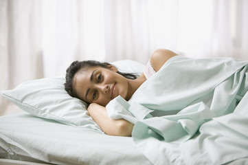Young adult woman laying in bed