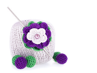 Ball of cotton yarn with knitted flower and beads on the white