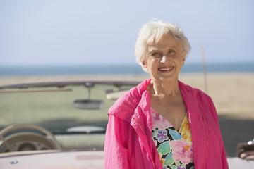 Senior woman next to convertible