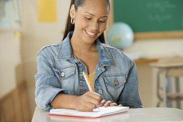 Female Dominican teenager writing in her notebook in classroom