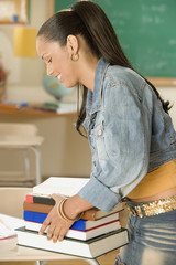 Female Dominican teenager picking up her books in classroom